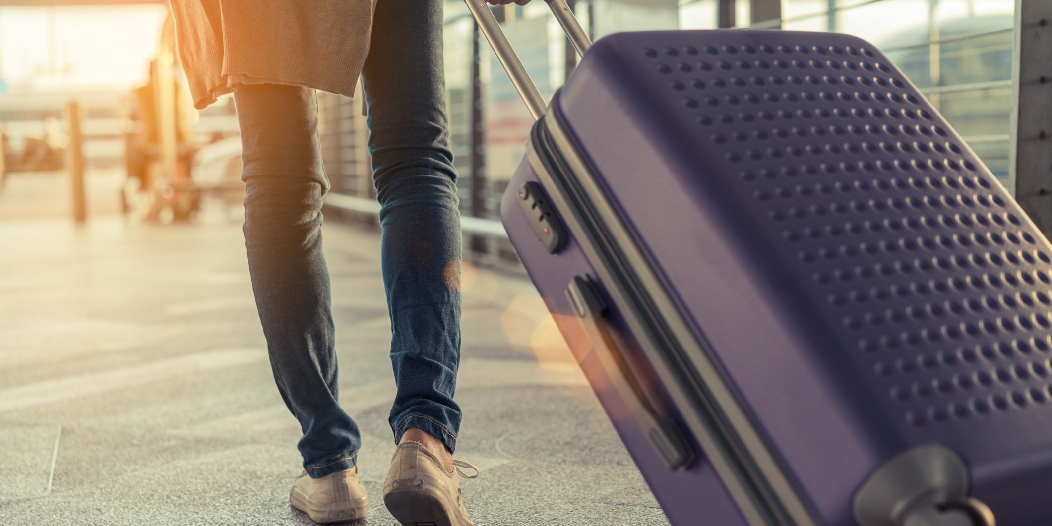 woman traveling in airport with suitcase