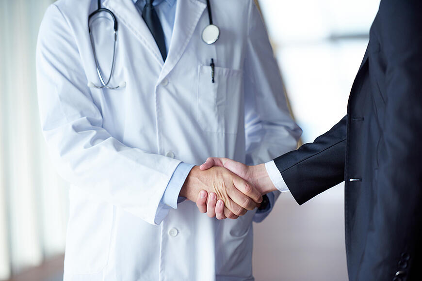 doctor handshake with a patient at doctors bright modern office in hospital-2